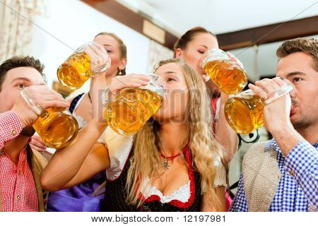 Inn or pub in Bavaria - group of five young men and women in traditional Tracht drinking beer and having a party with beer