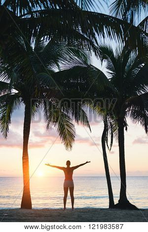 Blissful fitness woman enjoying outdoor summer relaxing sunrise or sunset at the beach after workout. Happy female athlete exercising during vacation under tropical palms at Riviera Maya Mexico.