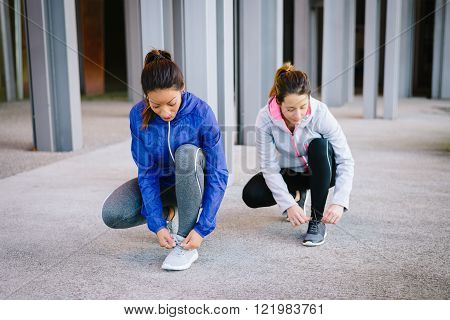 Two female athletes ready for urban running. Women getting ready for fitness workout and exercising.