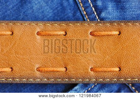 Leather brown belt on blue jeans. Background image.