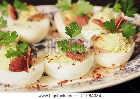 deviled eggs appetizer with avocado and bacon