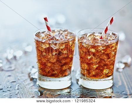 side by side glasses of ice cold cola soda pop with retro striped straws