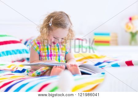 Cute curly little toddler girl reading a book sitting in a sunny bedroom on a wooden white bed with colorful rainbow bedding enjoying a nice weekend morning