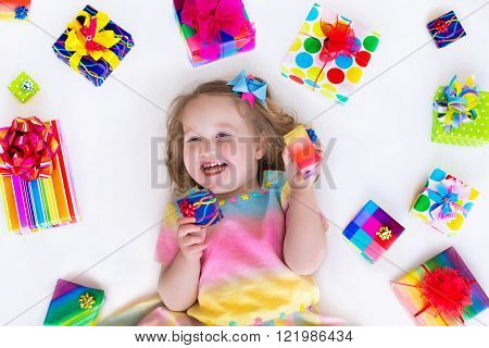 Happy laughing little girl adorable toddler in a colorful party dress holding many birthday presents opening boxes decorated with ribbon and bow excited to celebrate a family holiday