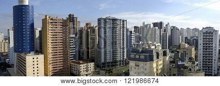 daytime panoramic view photograph of the city with blue sky and sun