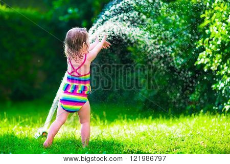 Child playing with garden sprinkler. Kid in bathing suit running and jumping. Kids gardening. Summer outdoor water fun. Children play with gardening hose watering flowers.