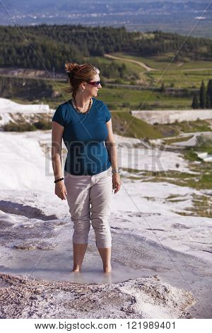 Pretty woman tourist wading in hot springs pool at Pamukkale