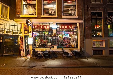 Amsterdam-May 01: Row of local steakhouses and restaurants at night in red-light district on May 01 2015 in Amsterdam the Netherlands.