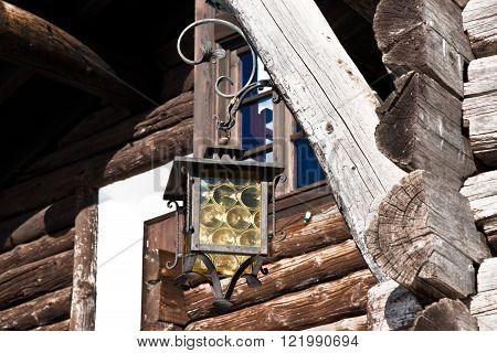old ferrous street lamp near wood house