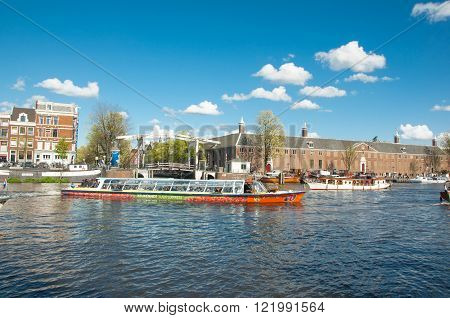 Amsterdam-April 30: Amsterdam cityscape tourists enjoy canal cruise Magere Brug (Skinny Bridge) and Hermitage Amsterdam are visible on the background on April 30 2015 the Netherlands.