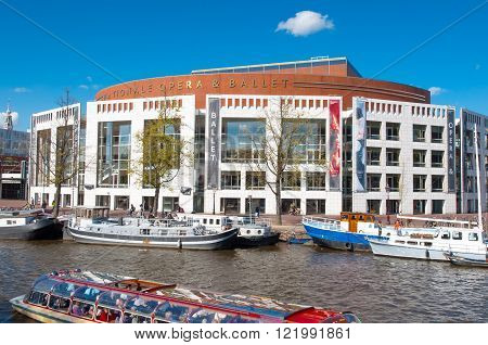 Amsterdam-April 30: Dutch National Opera & Ballet with boats along the bankon April 302015. The Stopera is a building complex housing both the city hall and the Dutch National Opera & Ballet.