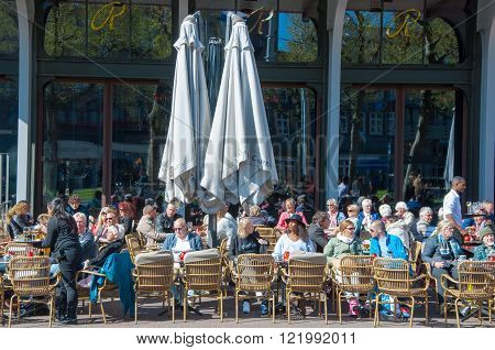 Amsterdam-April 30: Undefined people have drinks in outdoor cafe with Rembrandtplein view on April 30 2015 the Netherlands.