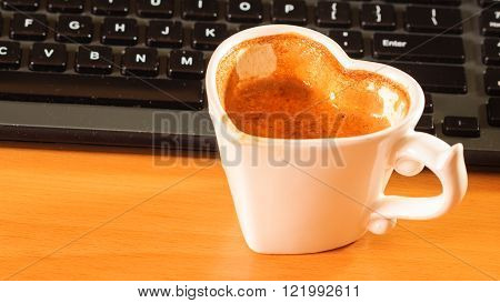 Heart shaped mug cup of coffee next to laptop notebook computer keyboard. Office work desk.