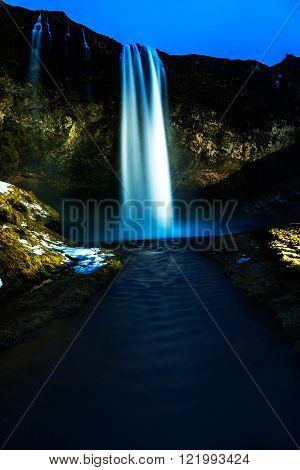 Seljalandsfoss waterfall at night, lit with strobes. Vertical composition