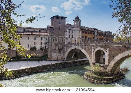 Rome, Italy - April 11, 2015 Green water of river Tiber surrounding the Island with historical buildings and an old bridge. Cloudy blue sky.