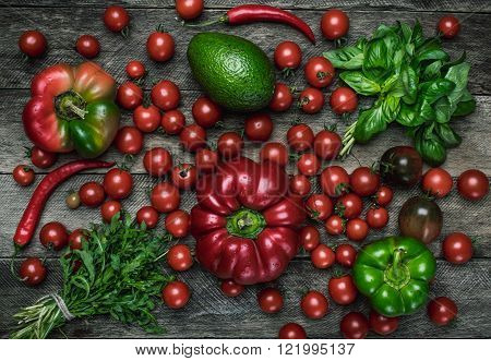 vegetables on wooden table in rustic style. Tomatoes pepper avocado basil
