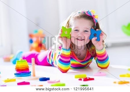 Child playing with wooden toys at preschool. Cute toddler girl having fun with toy blocks building a tower at home or day care. Educational kids toy for nursery or kindergarten.