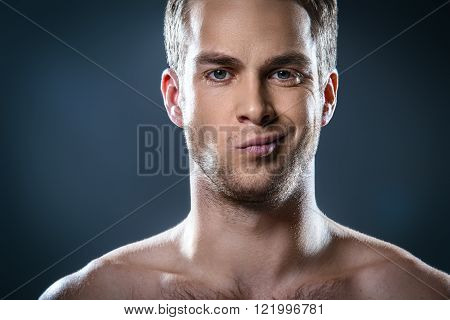 Studio portrait of handsome young man. Light unshaven and displeased man with naked torso looking at camera