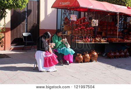 TEQUISQUIAPAN, QUERETARO/ MEXICO - FEBRUARY 21 2016: Indigenous embroidering and selling Mexican crafts