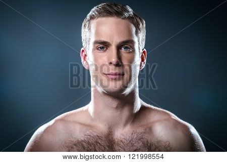 Studio portrait of handsome young man. Clean shaven man with naked torso looking at camera