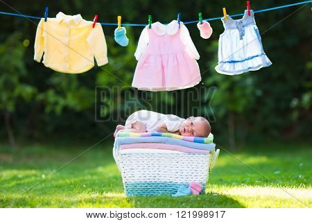 Newborn baby on a pile of clean dry towels. New born child after bath in a towel. Family washing clothes. Kids wear hanging on a line outdoors in summer garden. Infant apparel textile for children.
