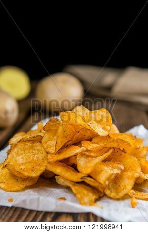 Portion of chilli Potato Chips (close-up shot) on wooden background