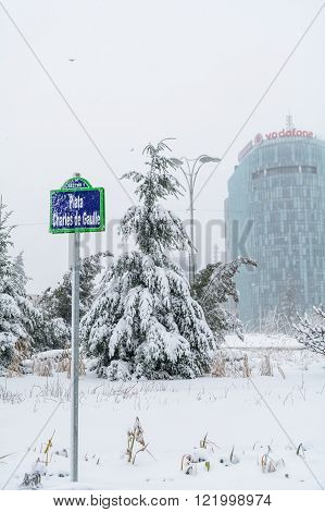 Bucharest, Romania - February 17: Plaza Charles De Gaulles on February 17, 2016 in Bucharest, Romania. Winter landscape with tree and skyscraper office building after a snow storm