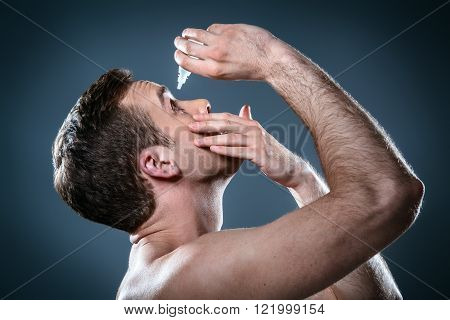 Studio portrait of handsome young man. Clean shaven man with naked torso looking at camera and using eye drops
