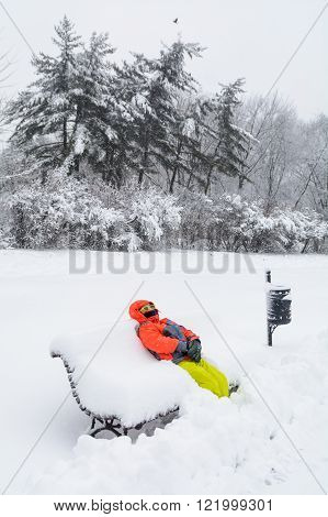 Little Boy Laying On Bench With Snow. Vertical View With Child In Winter Clothes Holding Hands And F