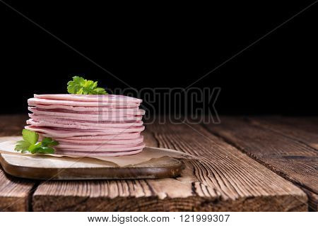 Old rustic wooden table with Ham Sausage (selective focus)