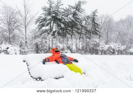 Little Boy Laying On Bench With Snow. Horizontal View With Child In Winter Clothes Spreading Hands A