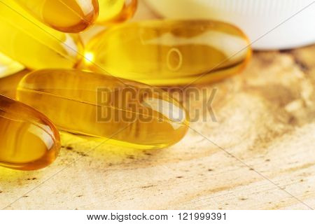 Fatty acid omega 3 fish oil gel capsules on wooden table macro image