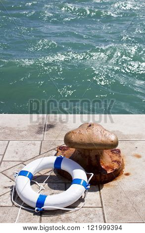Rusty iron bollard and white lifebuoy on a sea pier