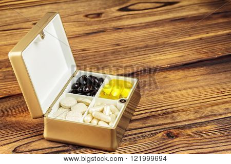 Mixed natural food supplement pills in container omega 3 vitamin c carotene capsules on wooden background