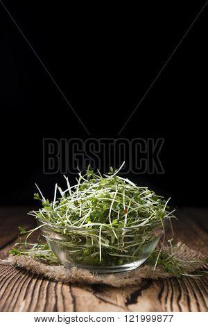 Portion of fresh Garden Cress (detailed close-up shot) on wooden background