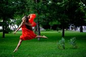 picture of beautiful woman  - Beautiful woman in red jumping in park - JPG