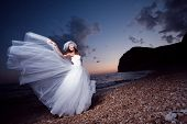 foto of night gown  - Bride posing showing her wedding dress on sunset beach - JPG