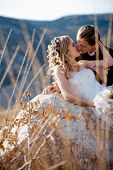 stock photo of wedding couple  - Kissing wedding couple on a stone outdoors - JPG