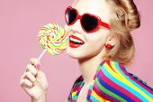 Glamourous girl wearing heart shaped sunglasses holding lollipop