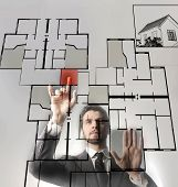 a businessman touching a digital blueprint of home