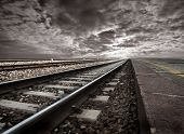 empty railway tracks in a stormy landscape