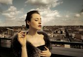 stock photo of snob  - a rich woman with fur and cigarette on top of a building - JPG