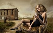 image of snob  - girl sitting on armchair with glass of wine in the countryside - JPG