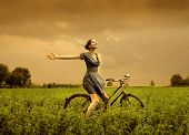 image of beauty nature  - beautiful girl riding bicycle in a grass field - JPG