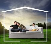 Young family seated on a sofa dreaming a home in the nature