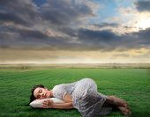 stock photo of nightgown  - woman in nightgown sleeping in a grass field - JPG