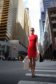stock photo of cross-dress  - attractive girl in red dress with shopping bags crossing a city street - JPG