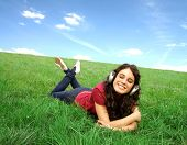Smiling young woman lying on a green meadow and listening to music through headphones