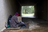 stock photo of underpass  - Homeless man finds shelter in damp underpass - JPG