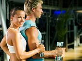Fitness couple in the gym, rivaling each other, exercising with weights (focus on the face of the gi